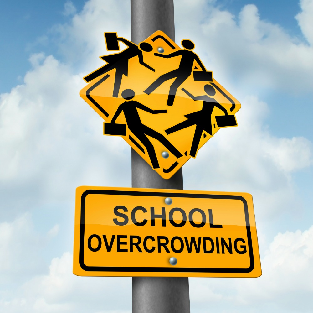School overcrowding and classroom overcrowding concept as a  crossing traffic sign with overcrowded students bursting out of the seams as a symbol of the problems of public education financing and lack of teachers.